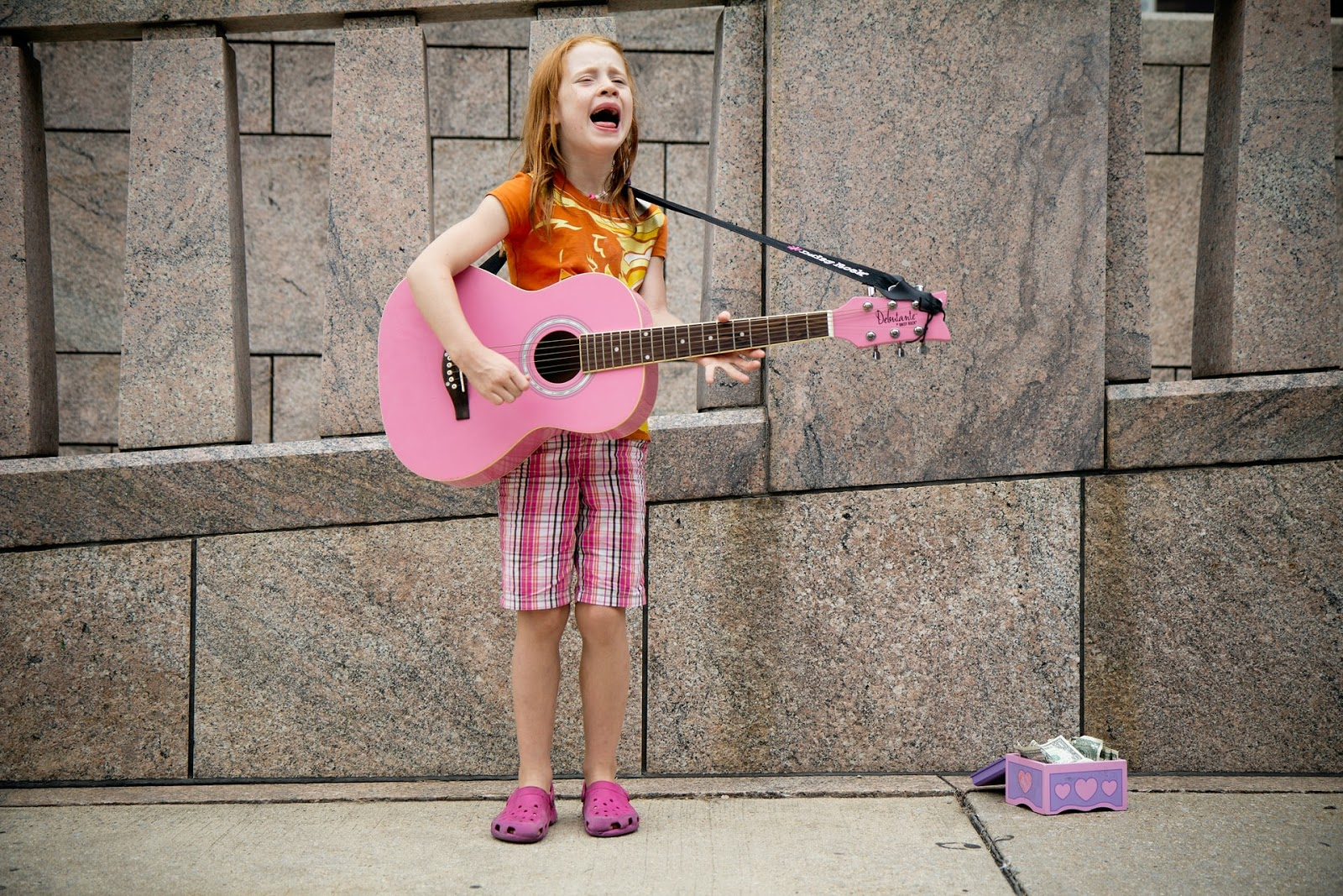 girl with a pink guitar singing after getting through a creative block