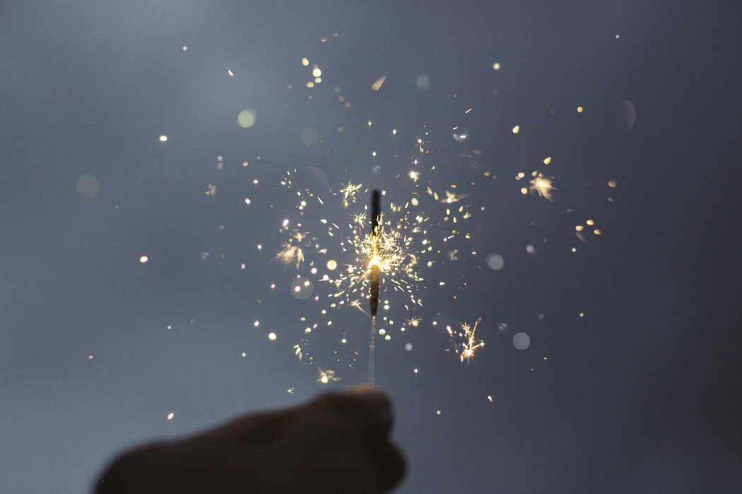 A silhouetted hand holding a sparkler halfway through burning