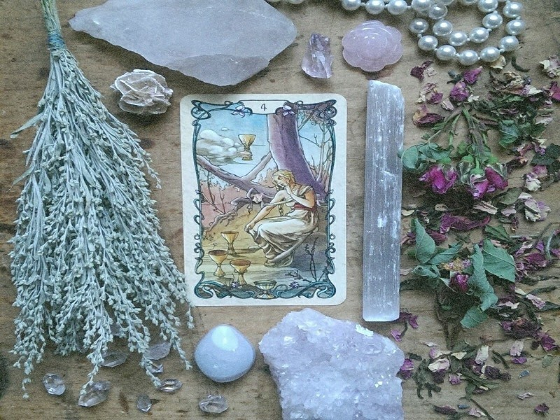Dried plants and flowers, crystals, and a pearl necklace surrounding a tarot card