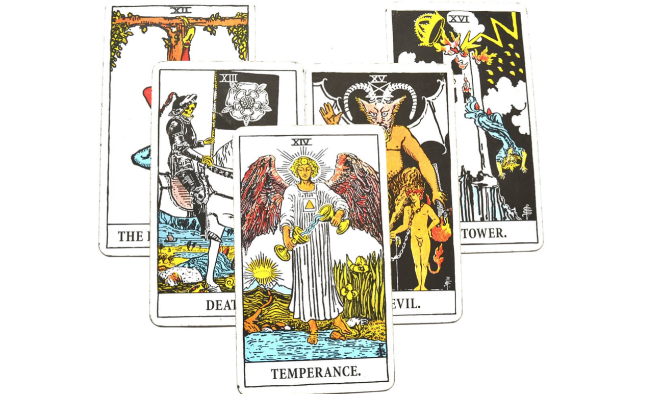 a stack of tarot cards with temperance on top