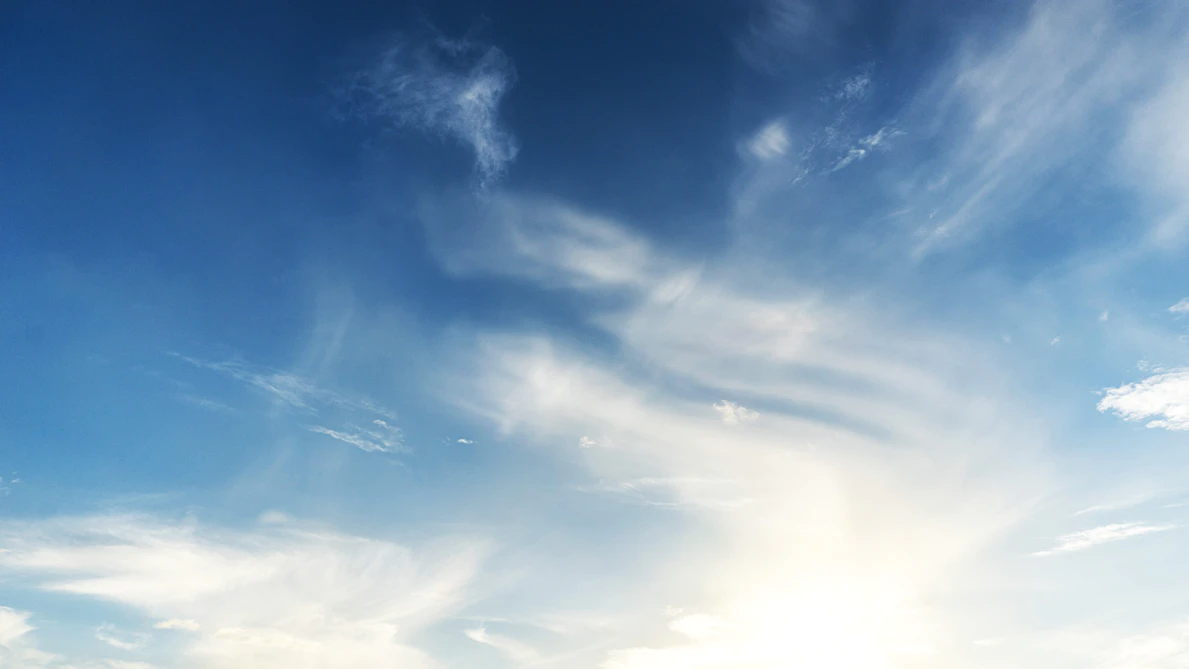 An expanse of blue sky with streaks of white, whispy clouds