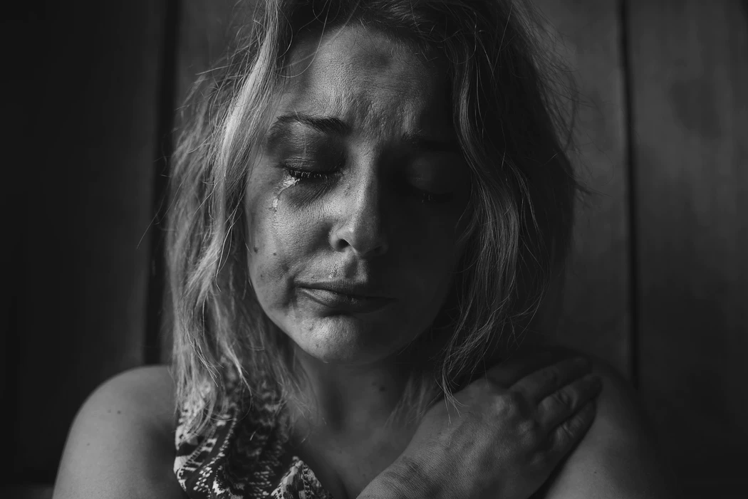 A black and white photo of a woman crying silently