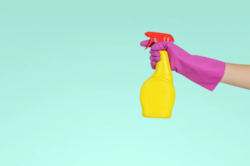 A purple-gloved hand weilding a bright red and yellow spray bottle against a teal background
