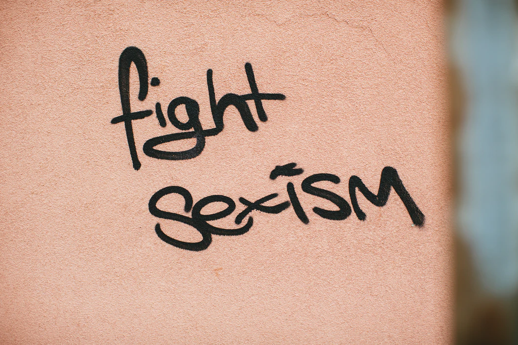 "The words ""fight sexism"" in black spray paint on a tan-colored wall"
