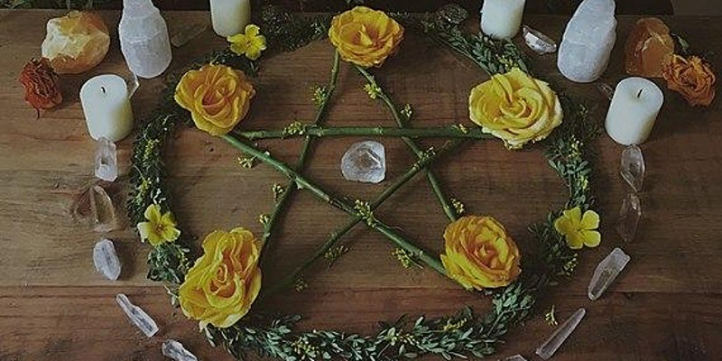 Samhain altar containing a pentagram, candles, and roses