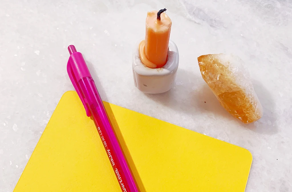 Picture of a pink pen, a yellow piece of paper, an orange candle and a brown crystal on a table