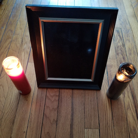 A rectangle-shaped black-colored mirror placed on the floor with a red candle on the left side and a black candle on the right side of the mirror