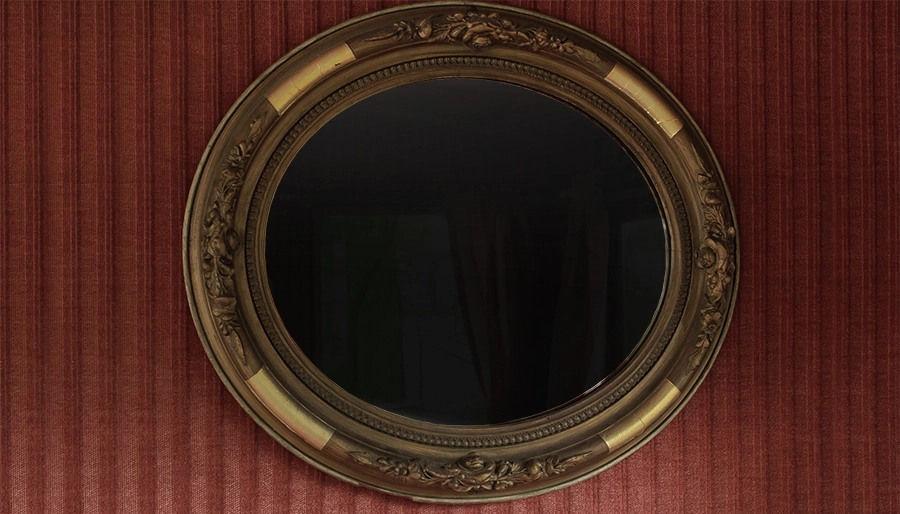 A circle-shaped black-colored mirror with a gold-colored frame