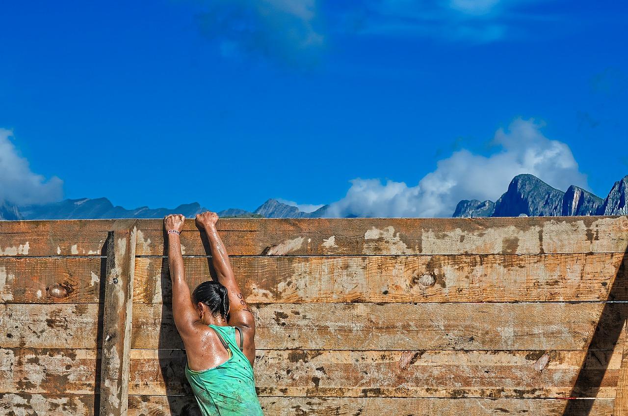 A person climbing over a wall.