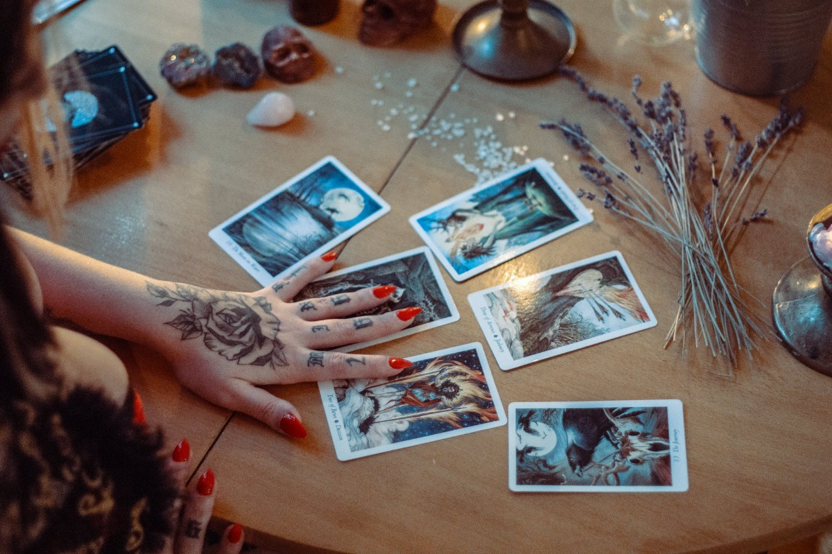 A spread of tarot cards on a table covered with flowers and crystals