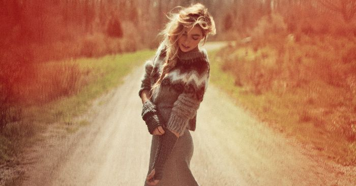 Picture of a woman in a sweater looking down on a country road sadly