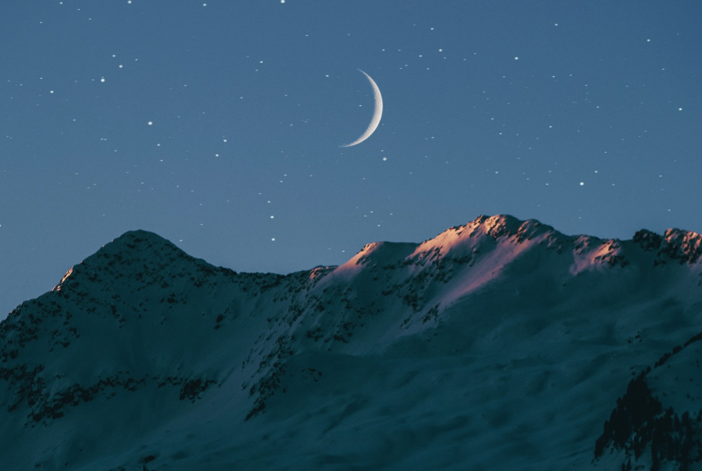 a waning crescent just before a new moon over a mountain range
