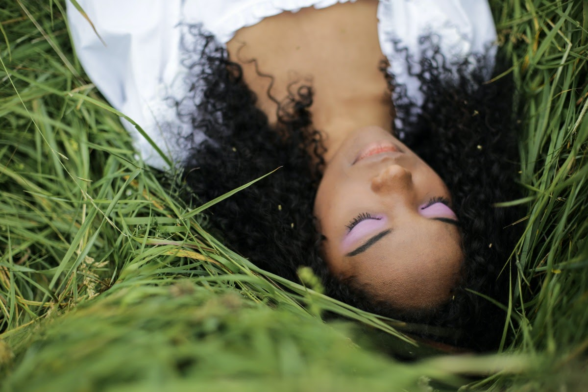 Black woman laying on the grass