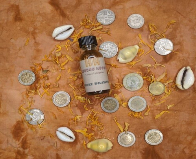 A bottle of essential oil surrounded by shells and coins