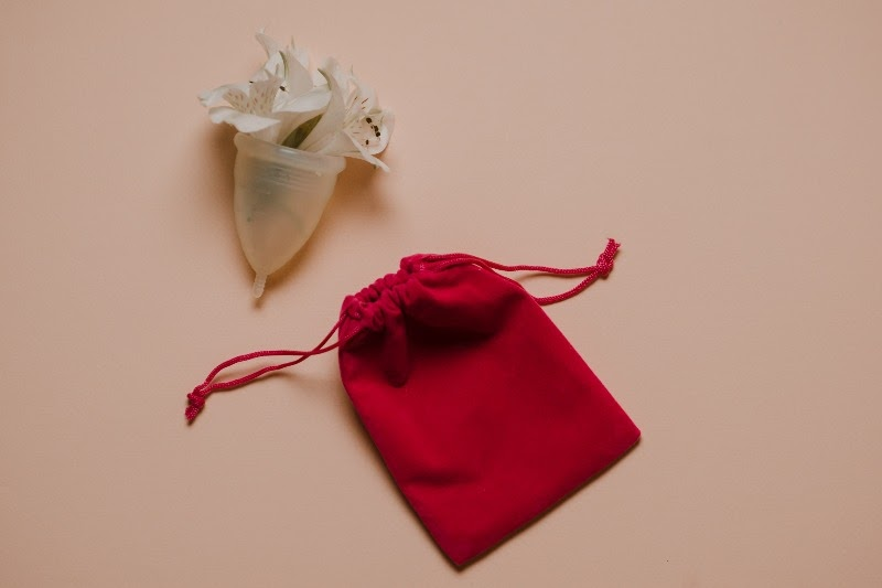 A menstrual cup with flowers inside of it a small pouch