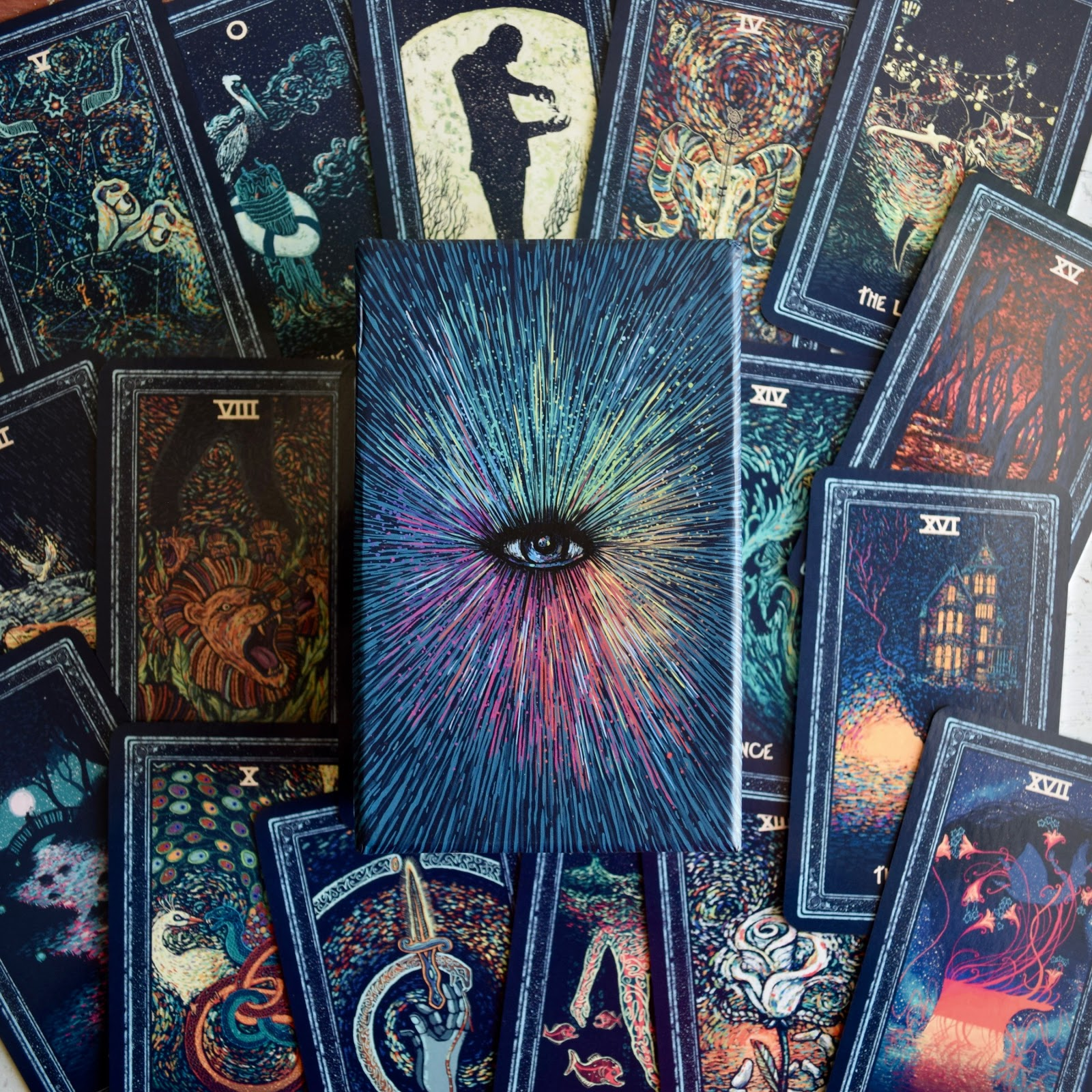 The box of the Prisma Visions Tarot Deck surrounded by blue tarot cards with vibrant images.