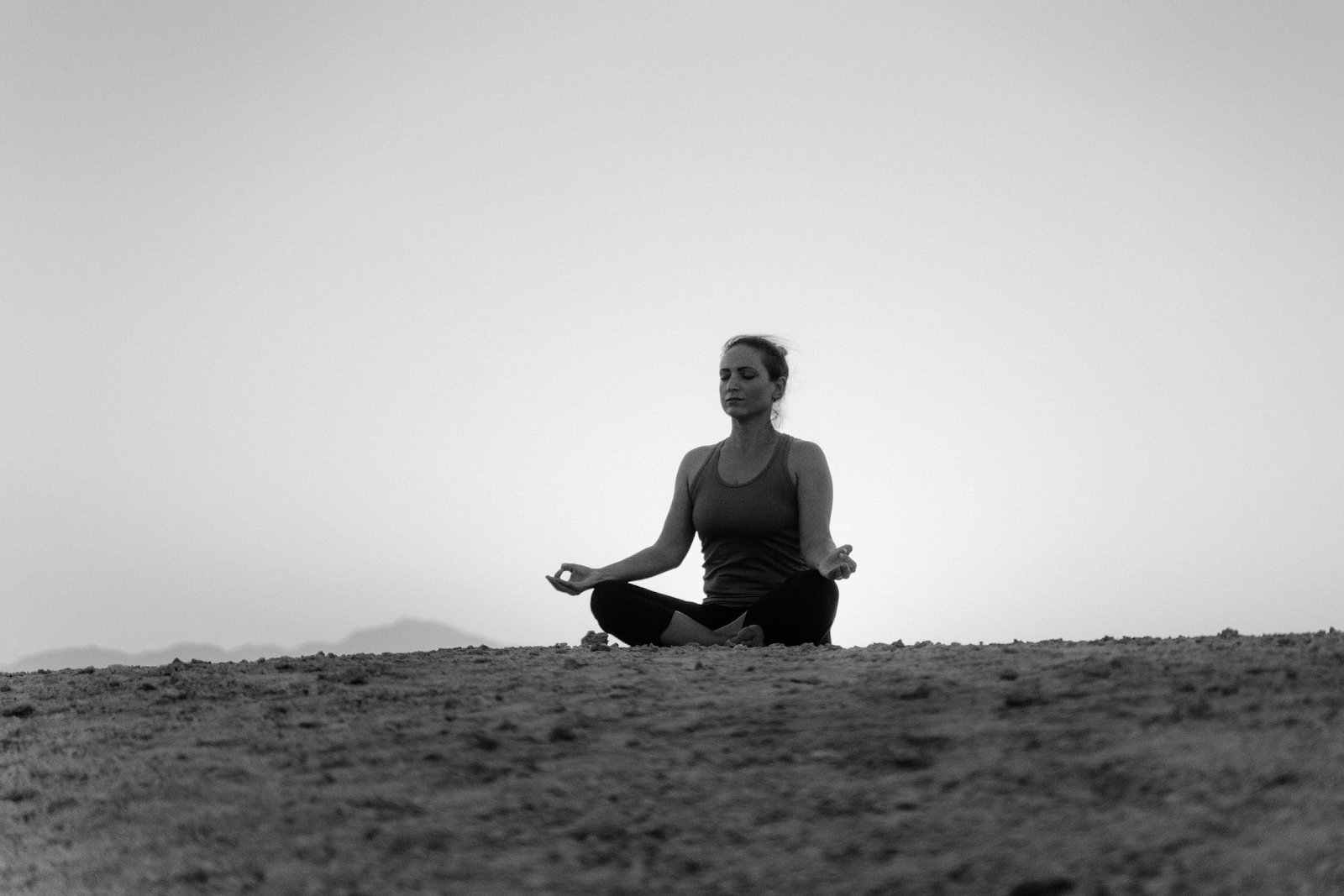Woman sits in the sun mudra pose, a pose focusing on opening the solar plexus chakra. Sitting cross-legged with her back straight and hands resting on her knees with her thumb and ring fingers touching.