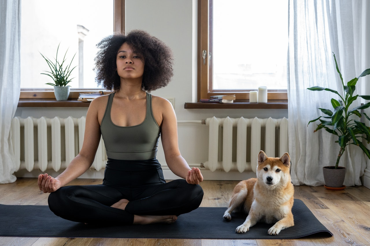 A young woman is sitting in a crossed leg pose on her yoga mat with her dog sitting to her left also on the yoga mat with her.