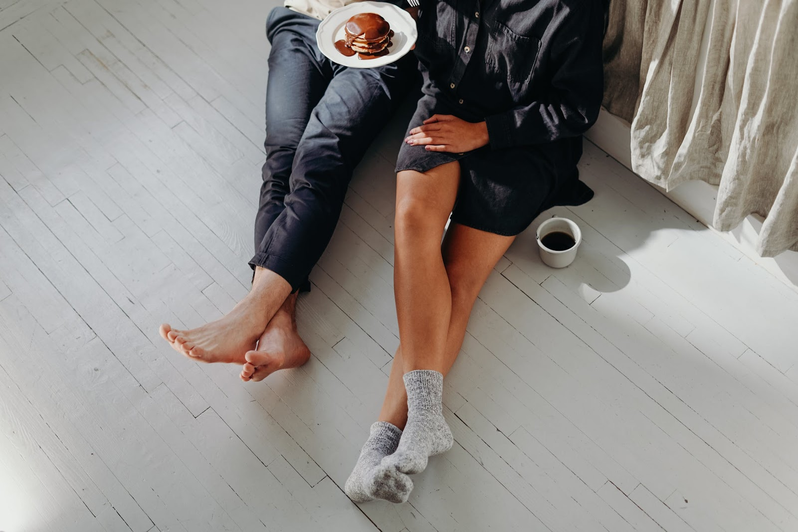 Two people sitting on the floor sharing a plate of pancakes.