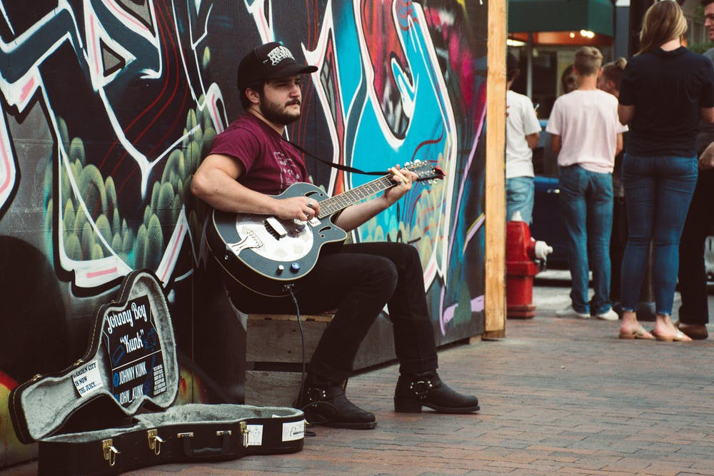 A busker sits in front of a colorful wall playing their guitar.