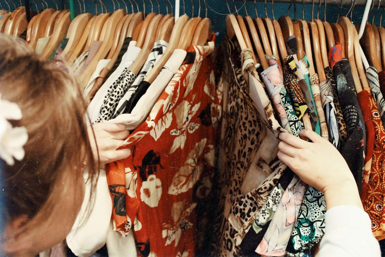 A woman looking through shirts on a clothes rack.