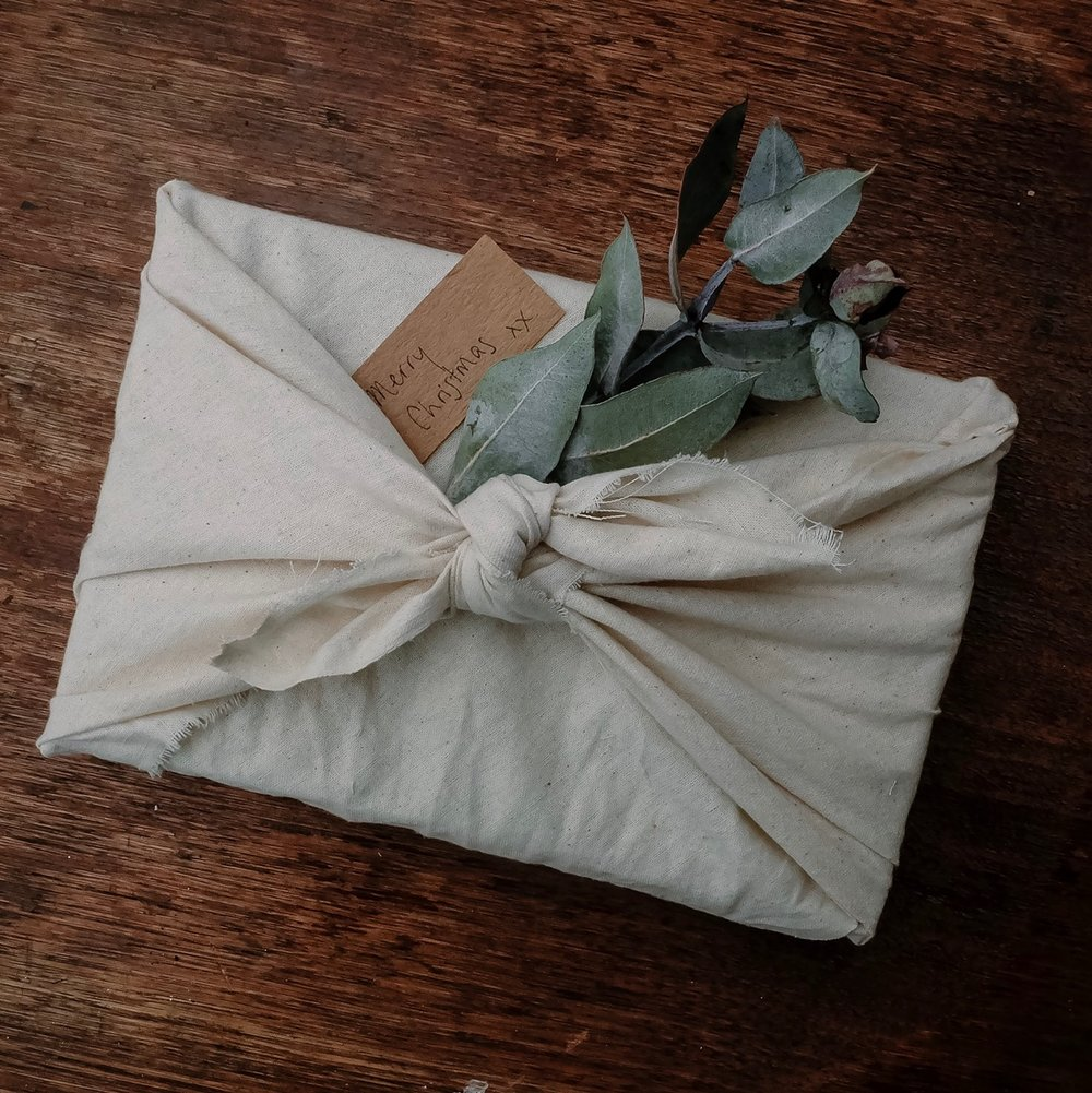 A cloth napkin used as eco-friendly wrapping, completed with a plant for decoration.