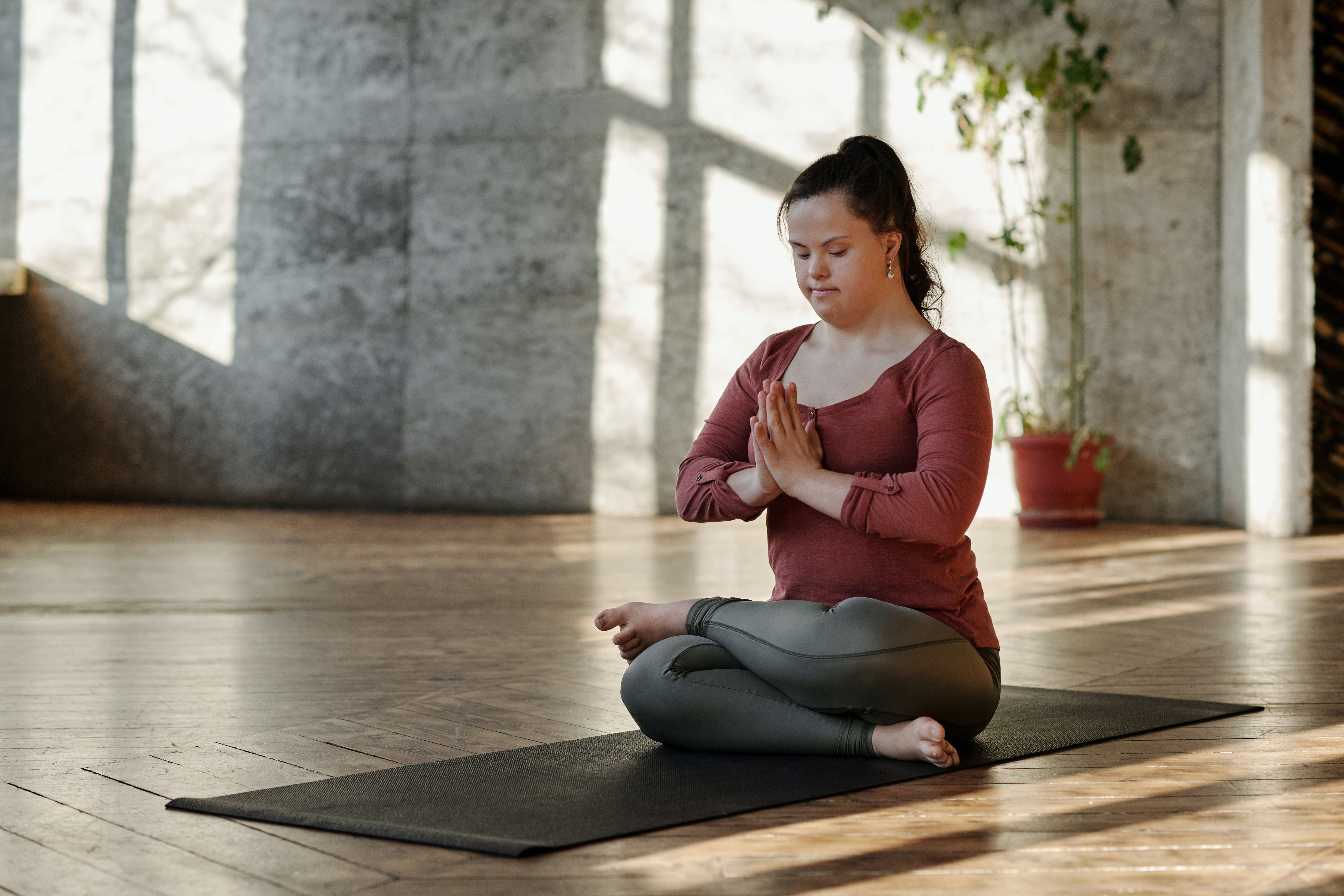 a young woman in a meditative posture on a yoga mat in a yoga studio