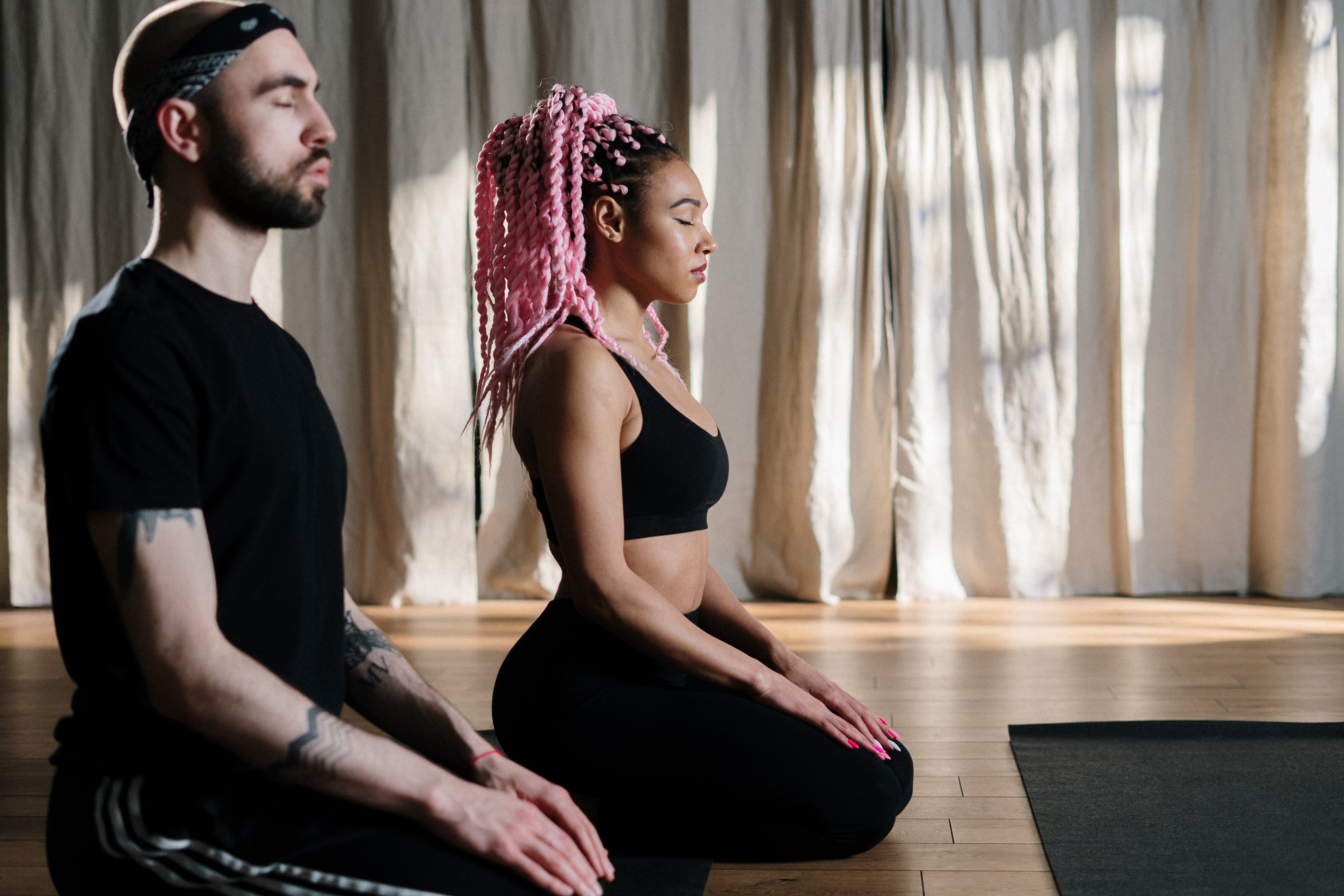 a man an a woman sitting on their knees in meditative postures with their eyes closed