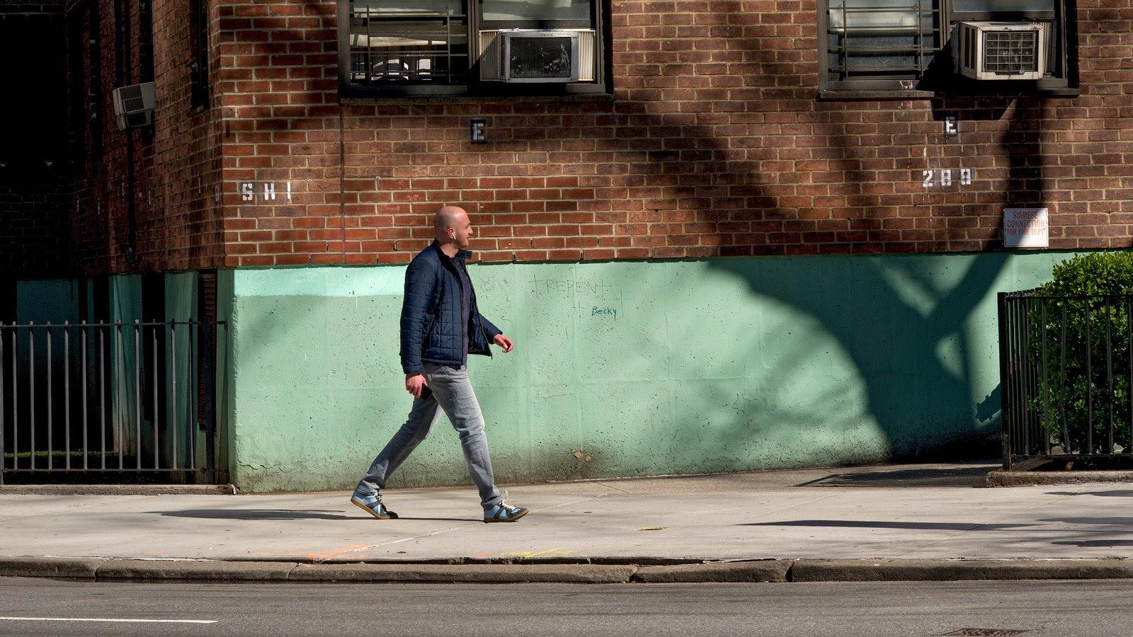 A man walking by himself on a sidewalk.