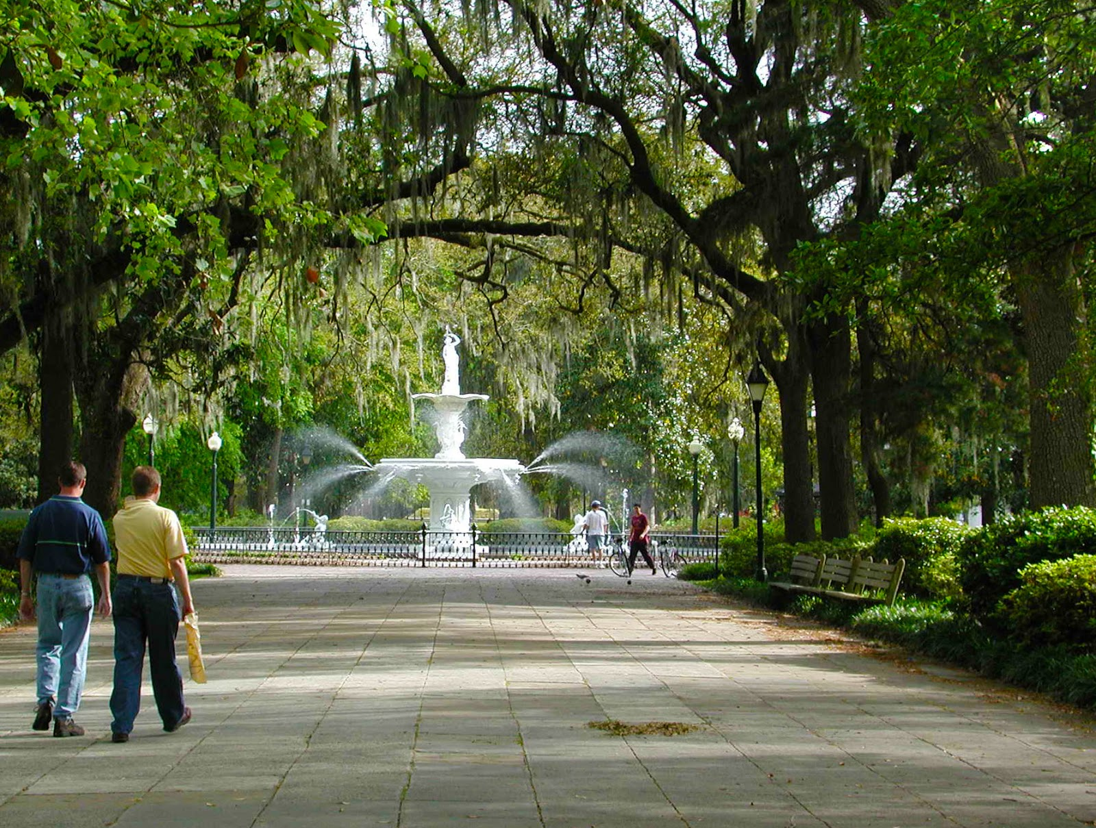 People walking around a fountain in a green space.