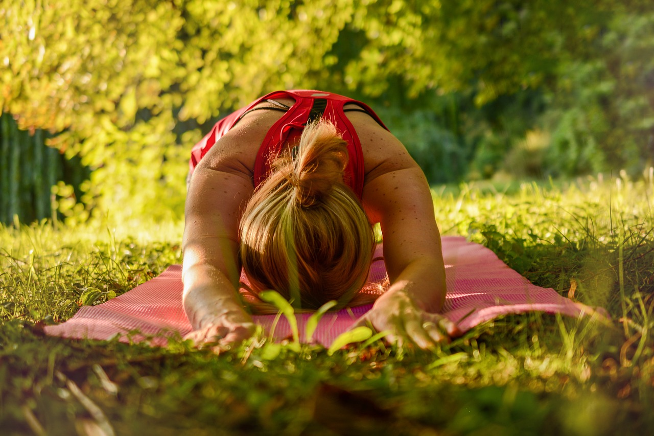 a woman in childs pose on a yoga mat in nature