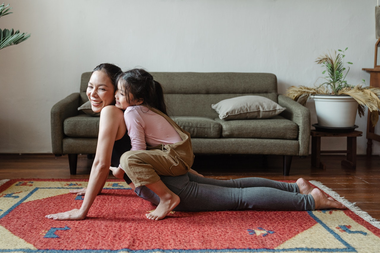 A mother doing cobra on her yoga mat with her daughter on her back