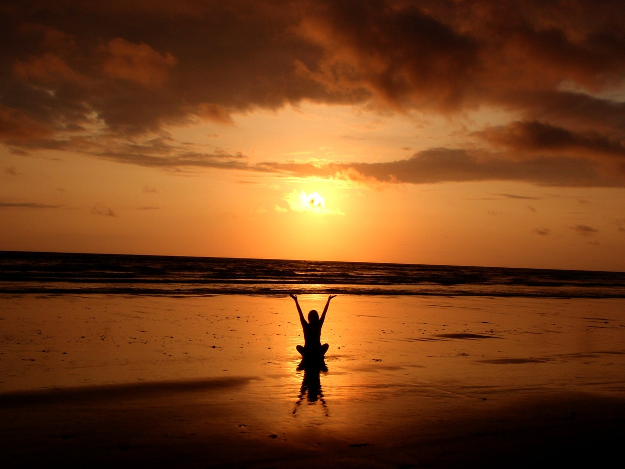 A person watching the sunset on a beach with their arms up in the air
