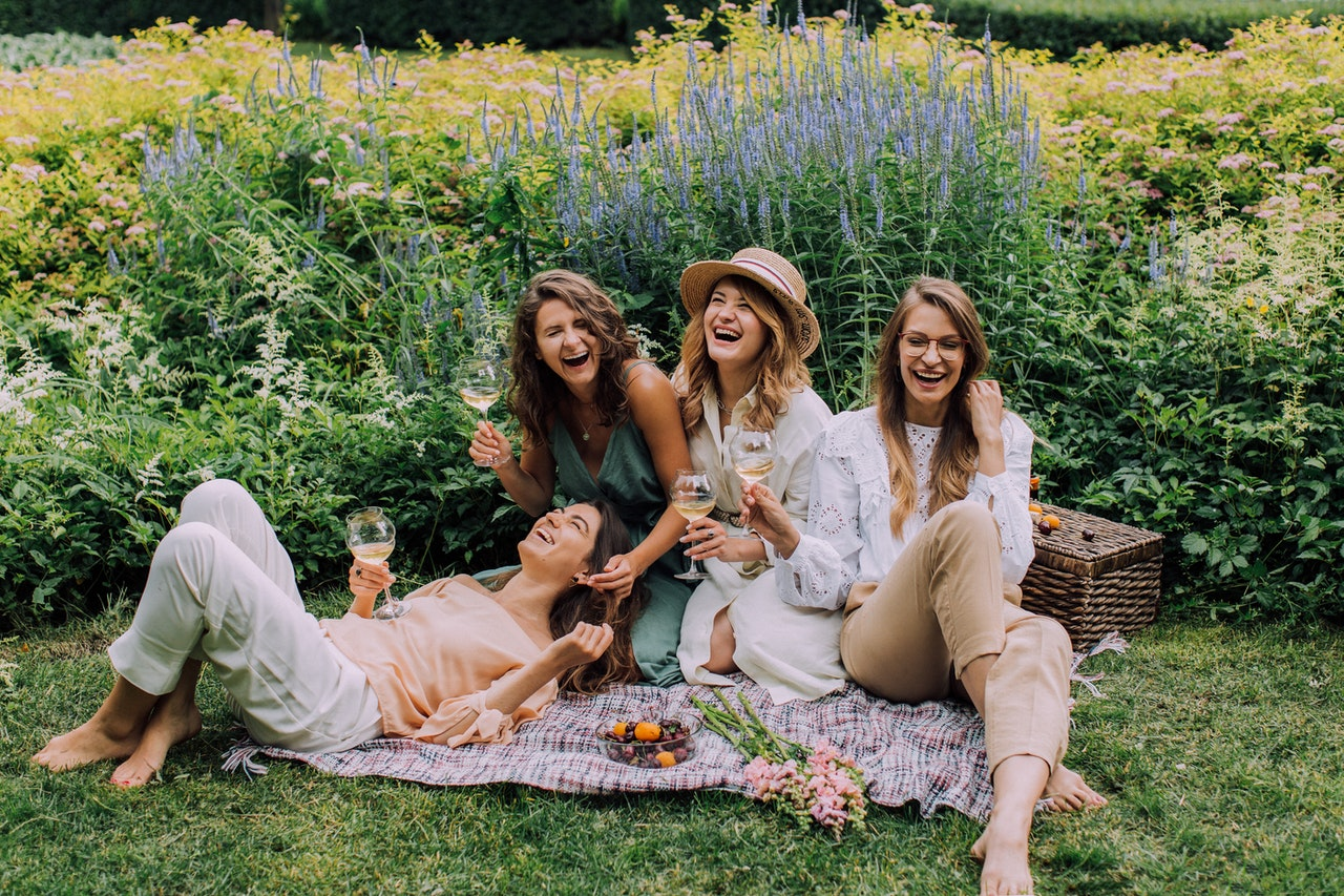 four friends laughing in a field of flowers at a picnic with win glasses in their hands.