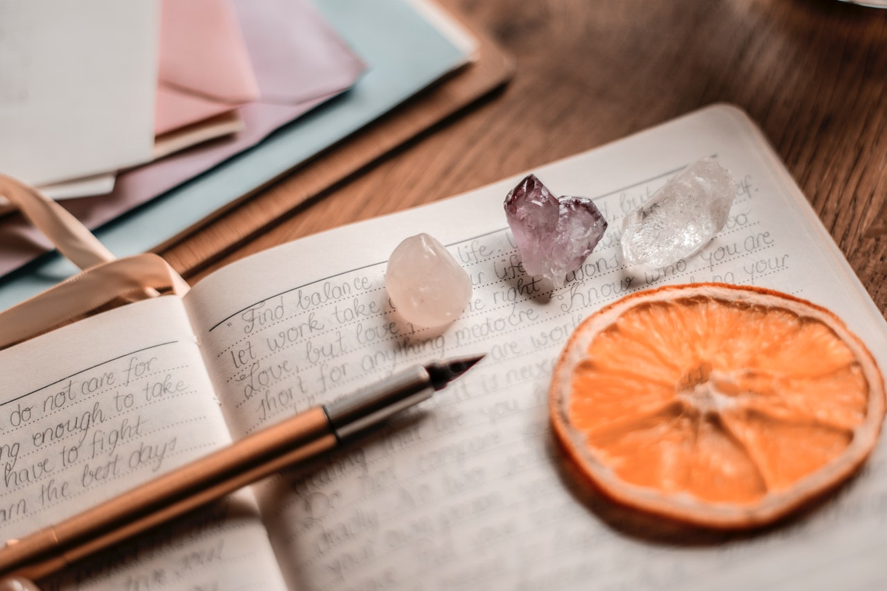 A journal with a pen, three crystals, and an orange slice sitting on the pages.