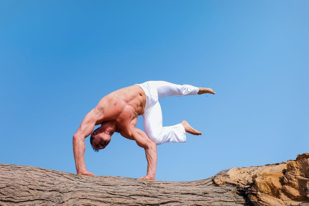 A man performs a yoga position against a blue sky.
