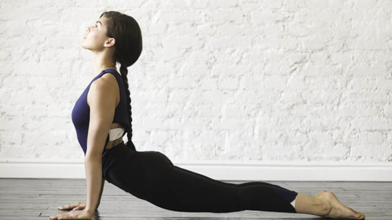 Woman practices vinyasa yoga in upward facing dog.