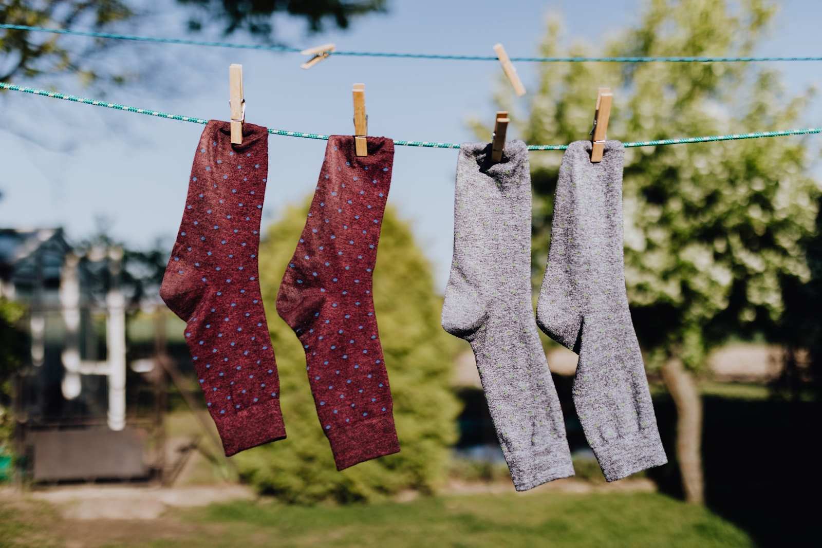 Socks hang drying on a clothes line to create a more eco friendly house.