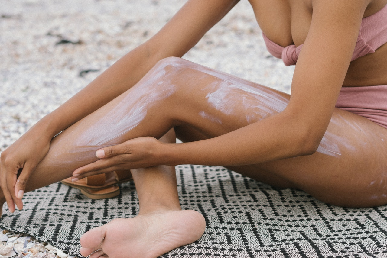 a woman putting sunscreen on her legs