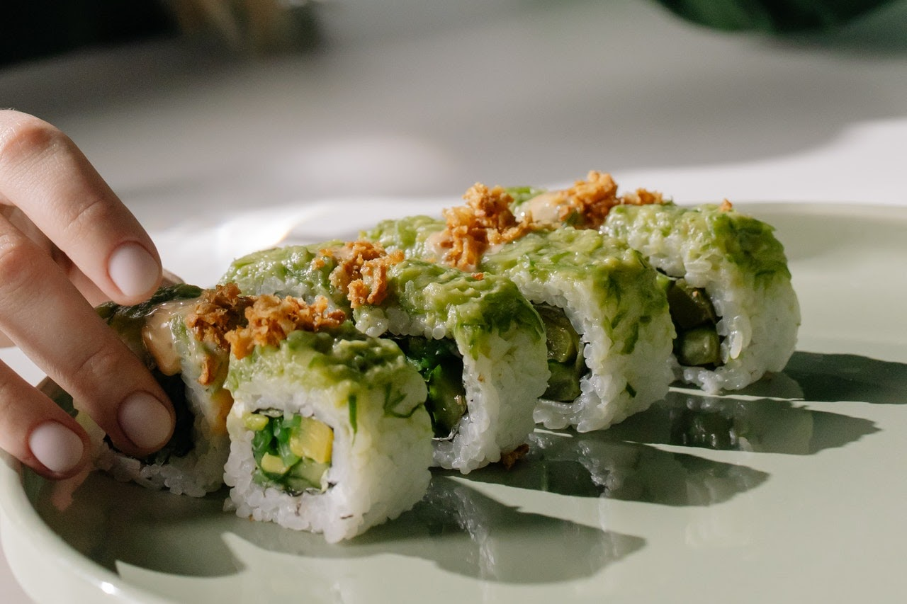 Two rolls of fish-free sushi with a hand grabbing a piece from the left side of the picture