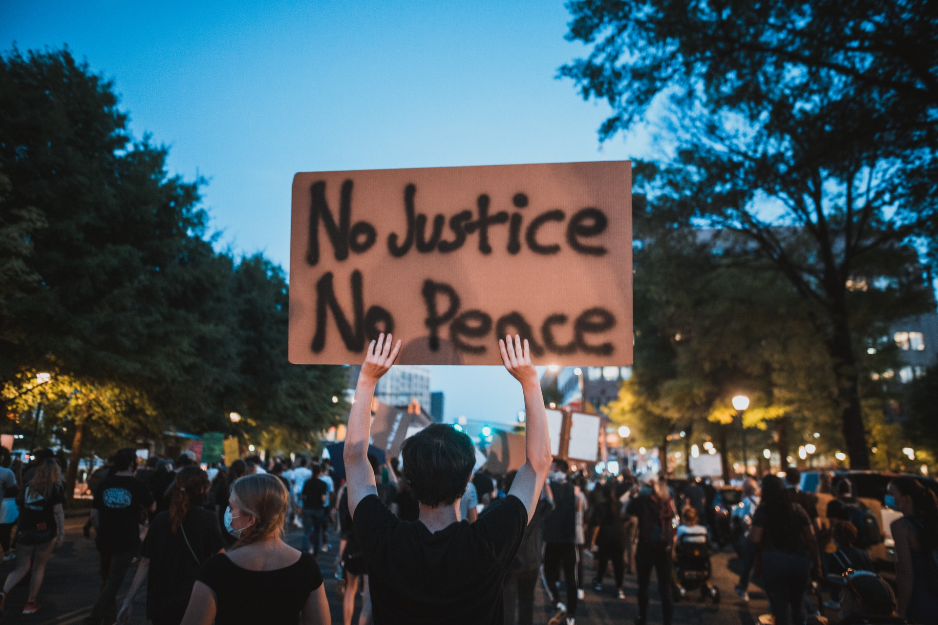 """A Black Lives Matter protestor holding a sign that reads """"No Justice No Peace."""""""