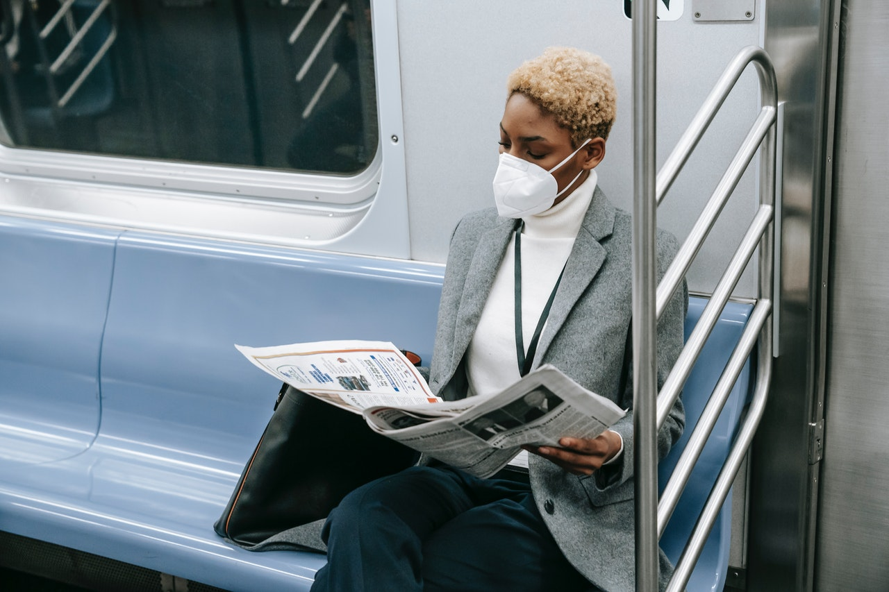 a woman with a mask reads the news paper on a subway