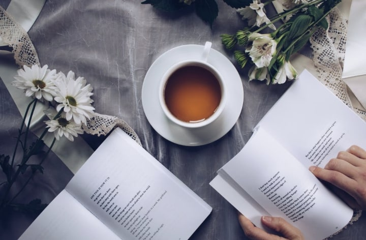 A dark hot tea is centered between two open books and two bunches of flowers.