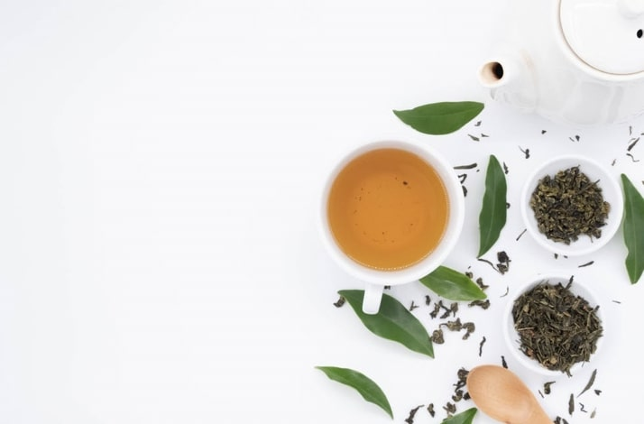 A light colored hot tea is to the right of the frame with leaves and two smaller bowls containing dry tea leaves are to the right