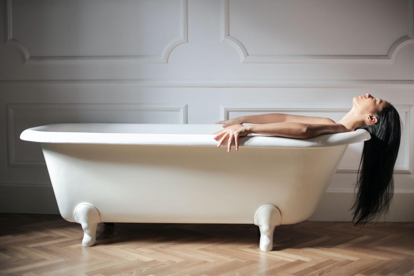 Woman laying back in a bathtub.