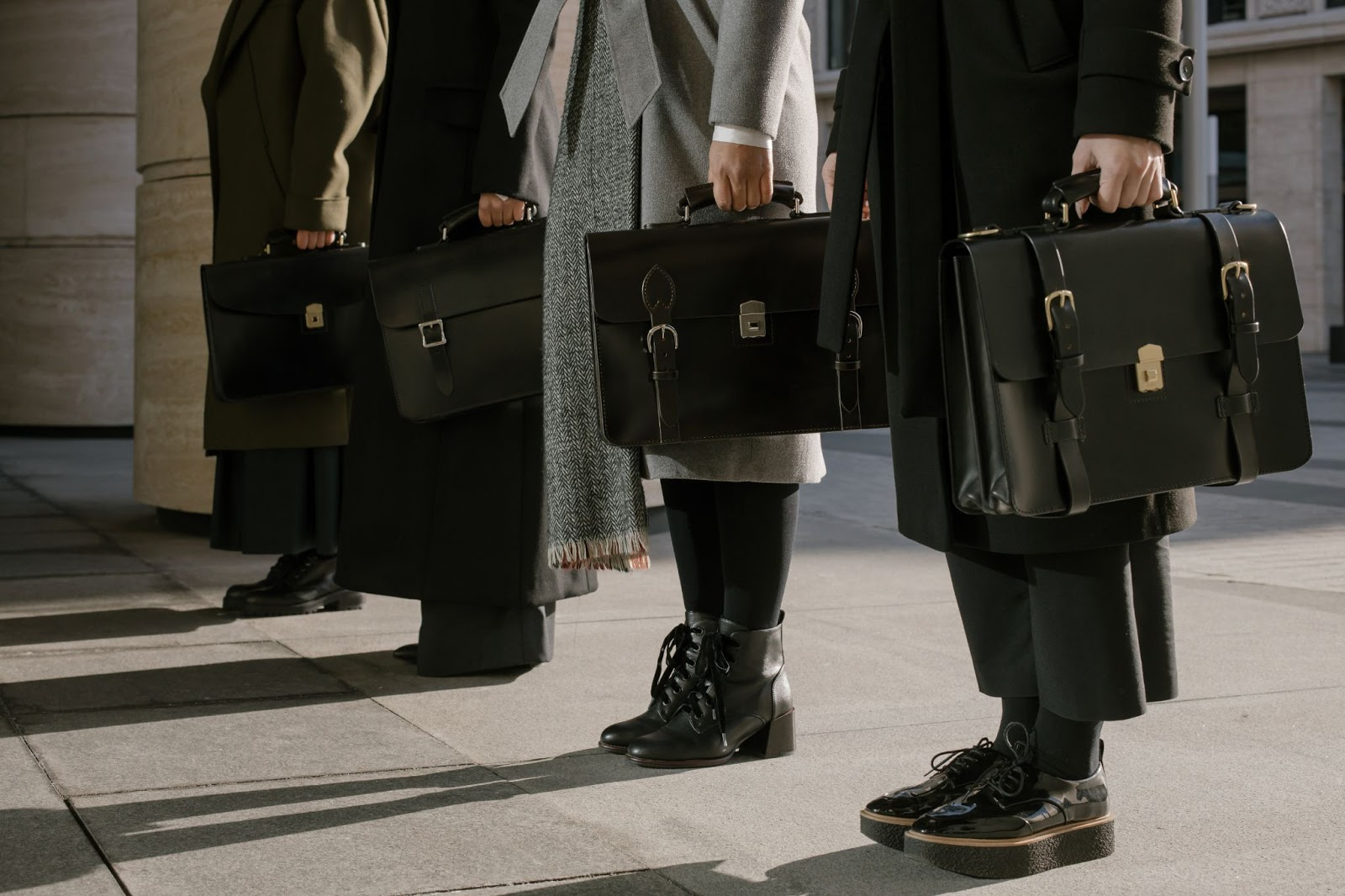 Line of people holding briefcases.