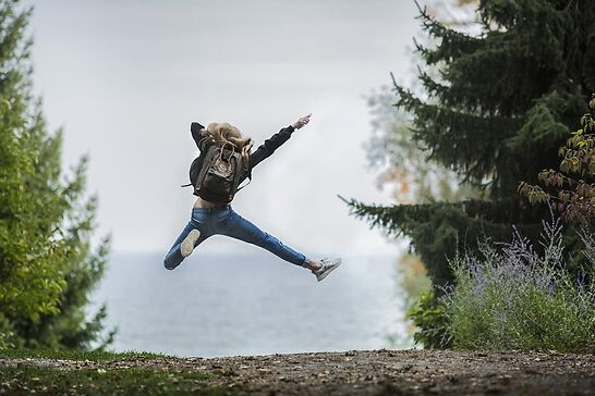 A girl in the forest jumping up in excitement.