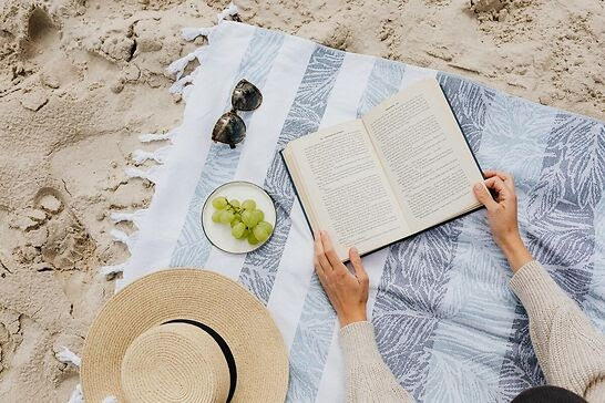 An open book, a hat, sunglasses, and grapes lying on a beach towel.