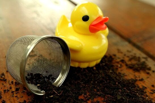 A yellow duck tea infuser with loose leaf tea scattered on the table.