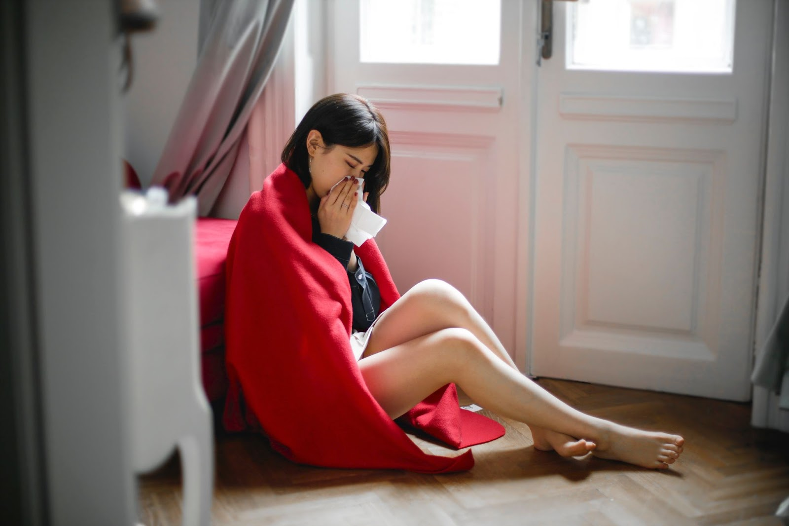 Crying woman wrapped in a blanket sitting on the floor with a tissue blowing her nose.